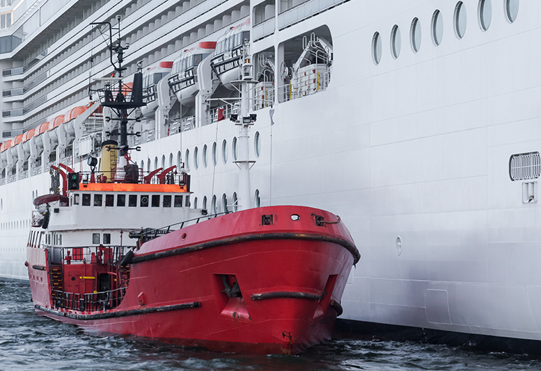 Red fuel vessel next to a large white cruise ship.
