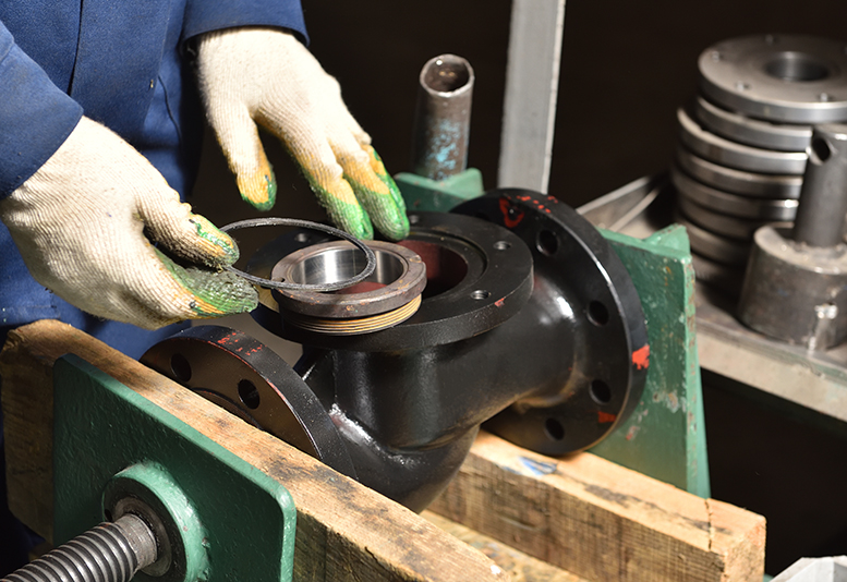 A person working sealing a portion of metal piping.