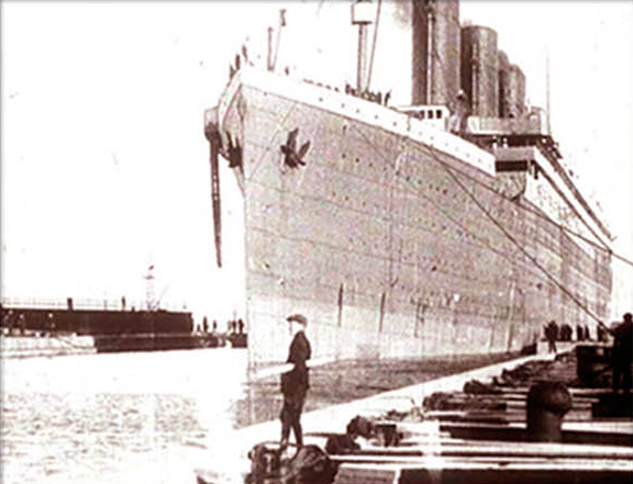 Old picture of man standing on a dock next to large vessel.