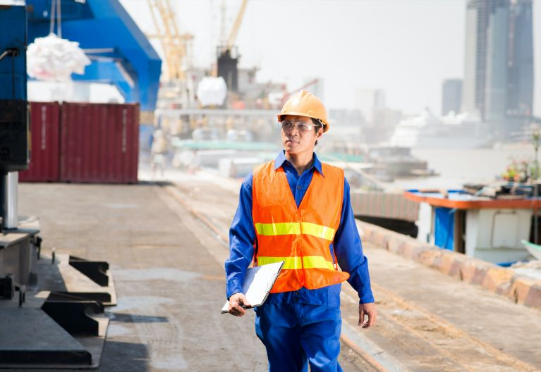 man wearing orange hard hat and vest walking on shipping rig.