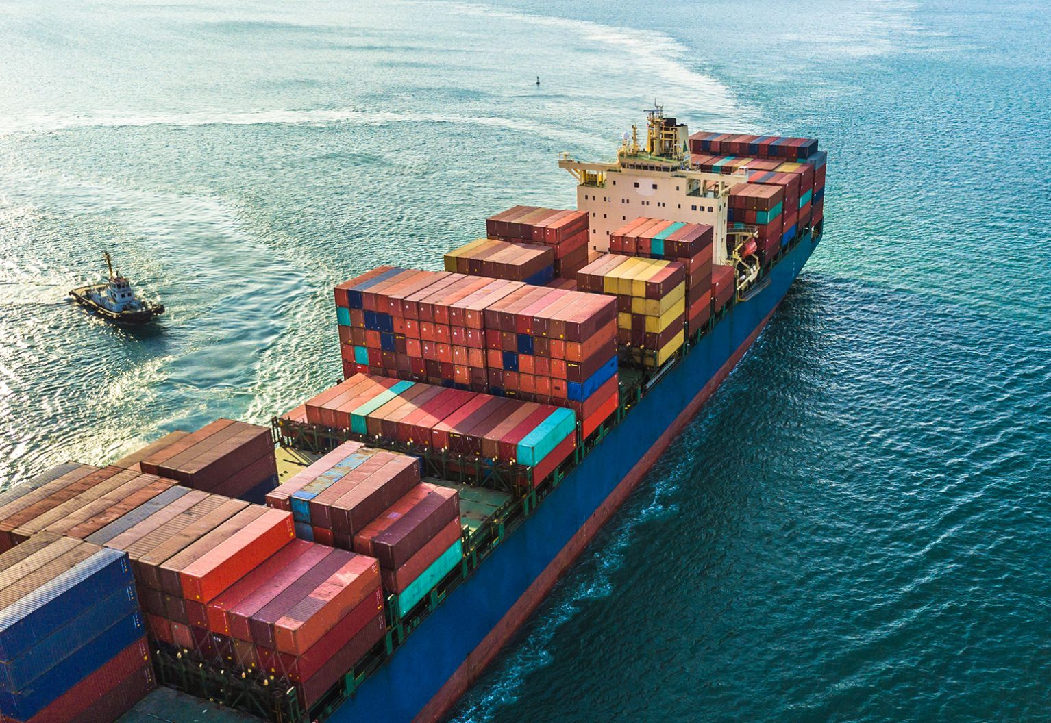 Large container ship carrying cargo with smaller ship next to it.