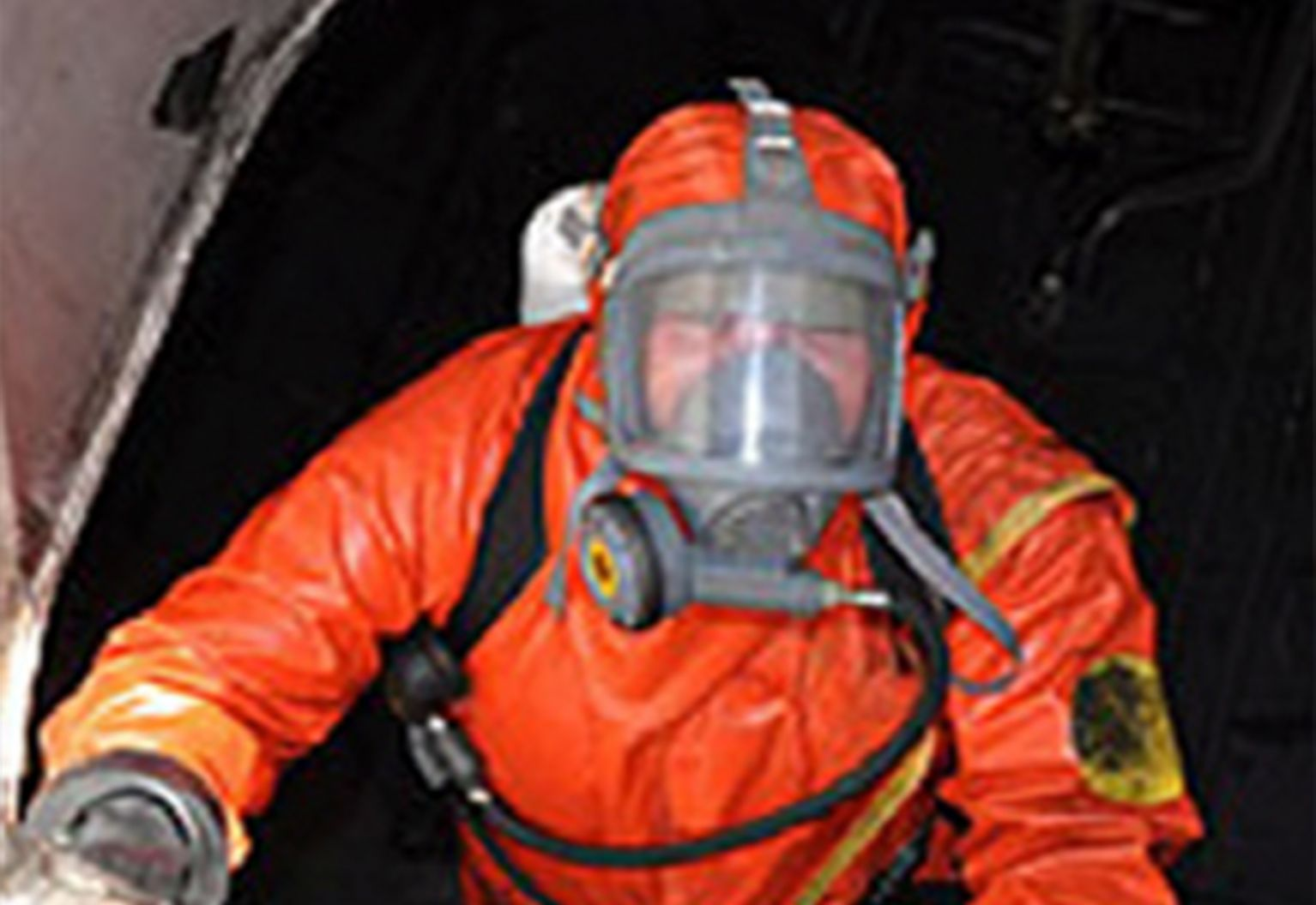 Man in orange wearing oxygen mask.