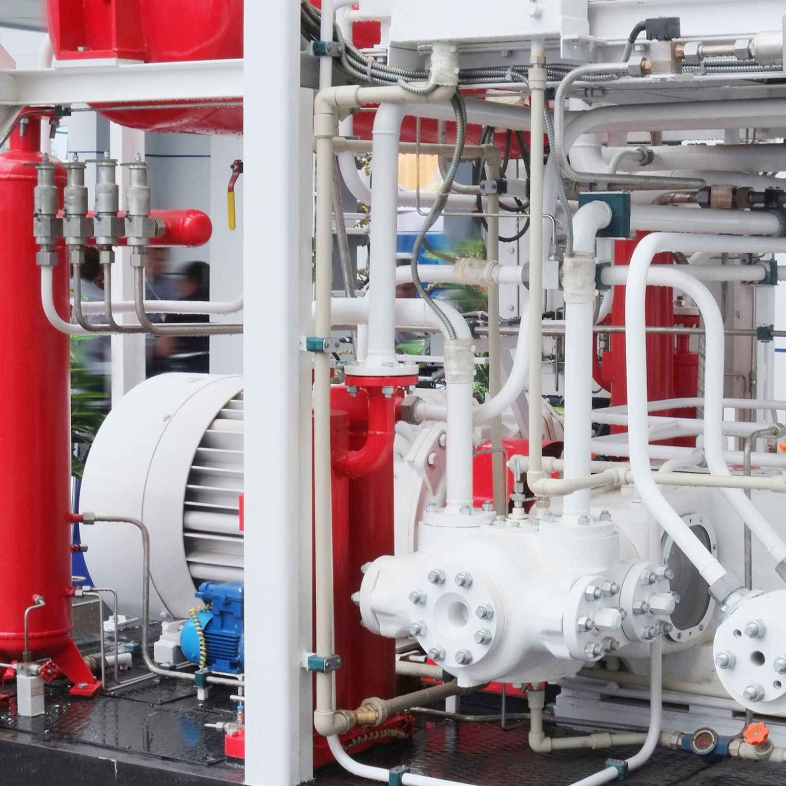 Red tanks surrounded by while piped and gauges.